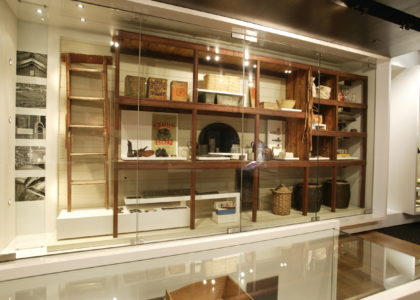 Wide shot of a museum display of old wooden shelving stacked with objects, inside a glass cabinet