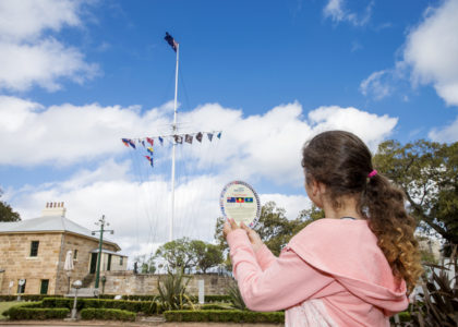 Girl holding up a disc with different flags and their names, to identify the flags flying on the flagstaff next to Sydney Observatory in the background