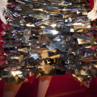 Close up view of a shiny silver metallic skirt made up of small panels