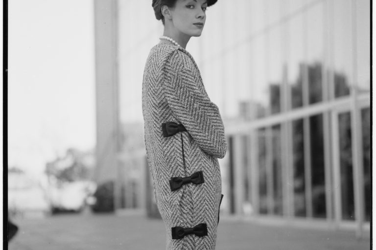 Bambi Shmith wears Hall Ludlow tweed 'Magpie' tunic over skirt and beret, tunic has black velvet bows down the side.