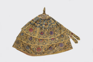 Photograph of an umbrella, made of Chinese Imperial yellow silk, cotton and bamboo, triple-flounced and embroidered with lotus flowers and scrolls. Click to view this object record on our Online Collection.