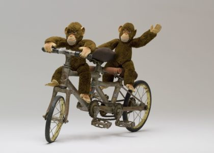Miniature tandem bicycle carrying two toy monkeys