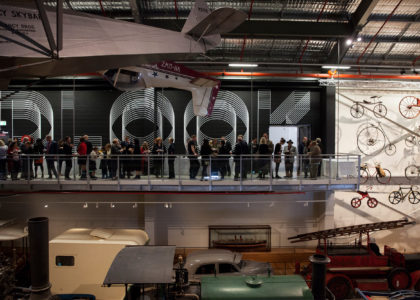 Wide shot of visitors at the MDC, standing on the indoor balcony overlooking objects below and talking to each other