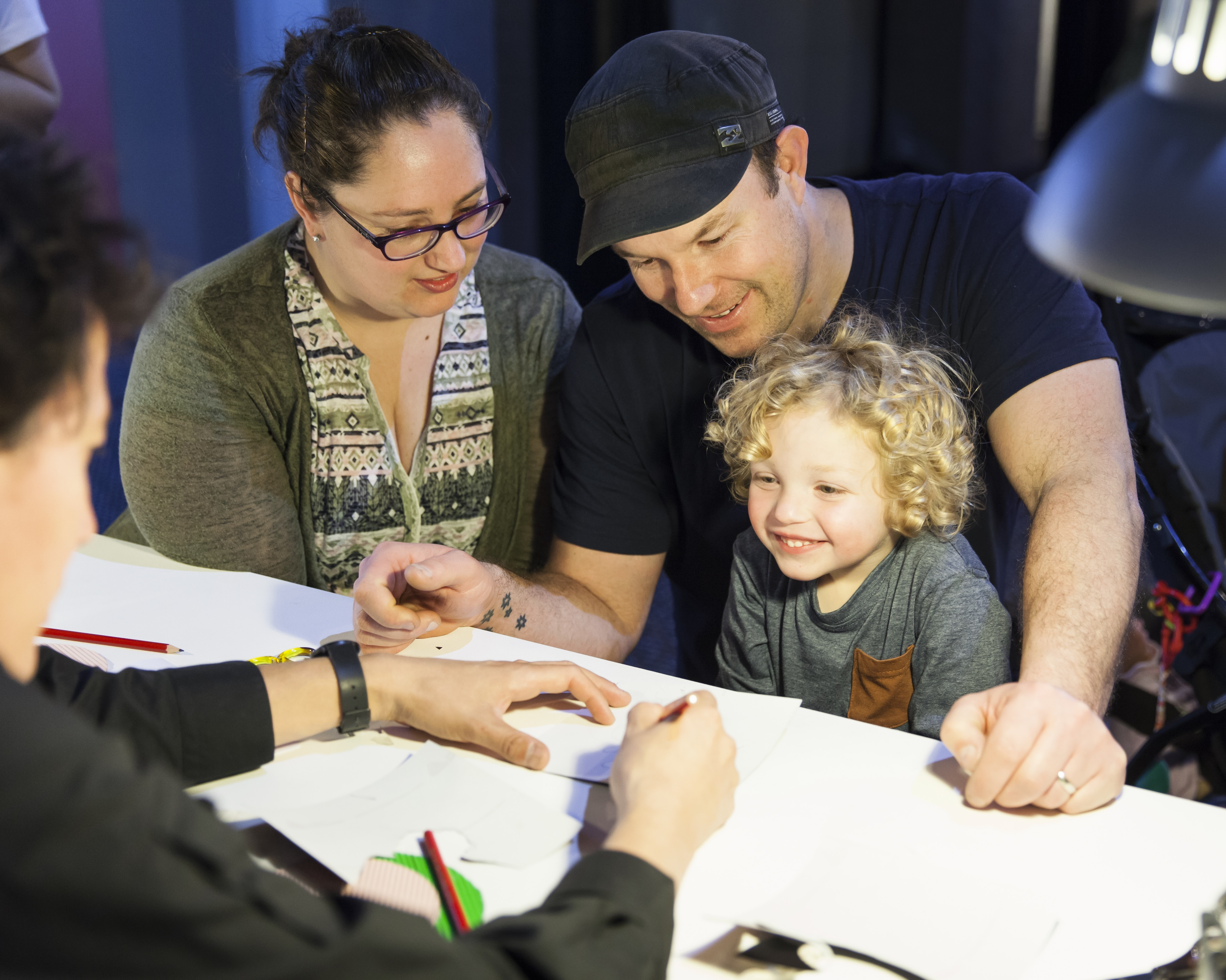 Family group, woman, man and child with blonde curly hair smiling as they watch woman draw.