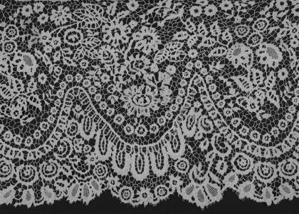 Carrickmacross lace, design features a scalloped shape border with a scrolling floral pattern with daisy shaped flowers, tulip shaped flowers, leaves and vines.