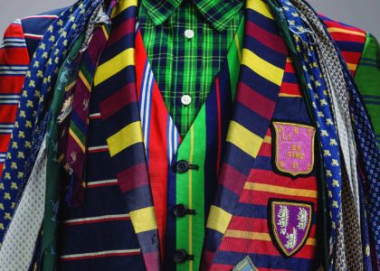 Close up of a torso adorned with colourful layered men's fashion garments