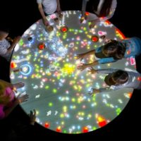 A table with light projections of little people, surrounded by children.