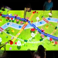 A table with light projections of a map depicting a town with roads and vehicles