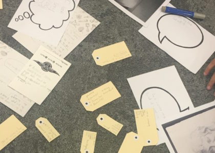 Hands sort through notecards, outlines of speech bubbles and photos scattered on a surface