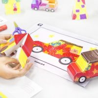 Coloured-in picture of a car next to a 3D paper craft version of the same car