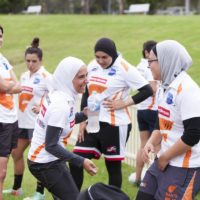Auburn Giants (formerly Tigers) football team at training session at the University Western Sydney, Milperra campus AFL field, for Faith, fashion, fusion: Muslim women's style in Australia travelling exhibition. Women wearing headscarves, hijabs and playing football.