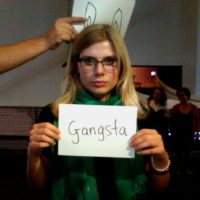 Woman holding up sign which reads, gangsta 1