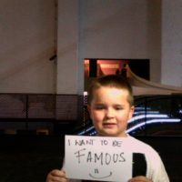 Boy holding sign that reads, I want to be famous