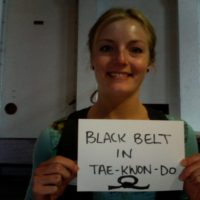 Woman holding up sign which reads, Black-belt