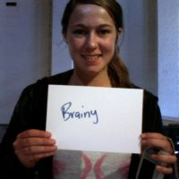 Woman holding up sign which reads, Brainy