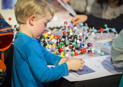 Young boy playing with atom molecular models