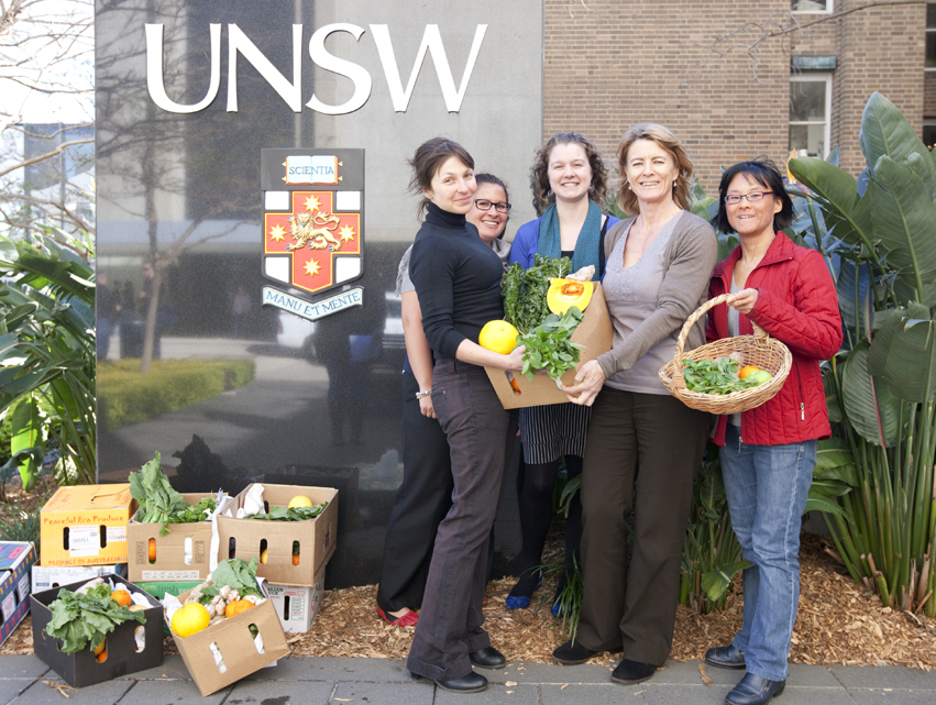 Five women stand holding boxes of fresh vegetables at the University of NSW.
