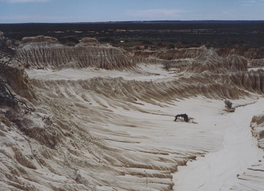 A dry lake bed with deep ridges caused wind and water erosion.