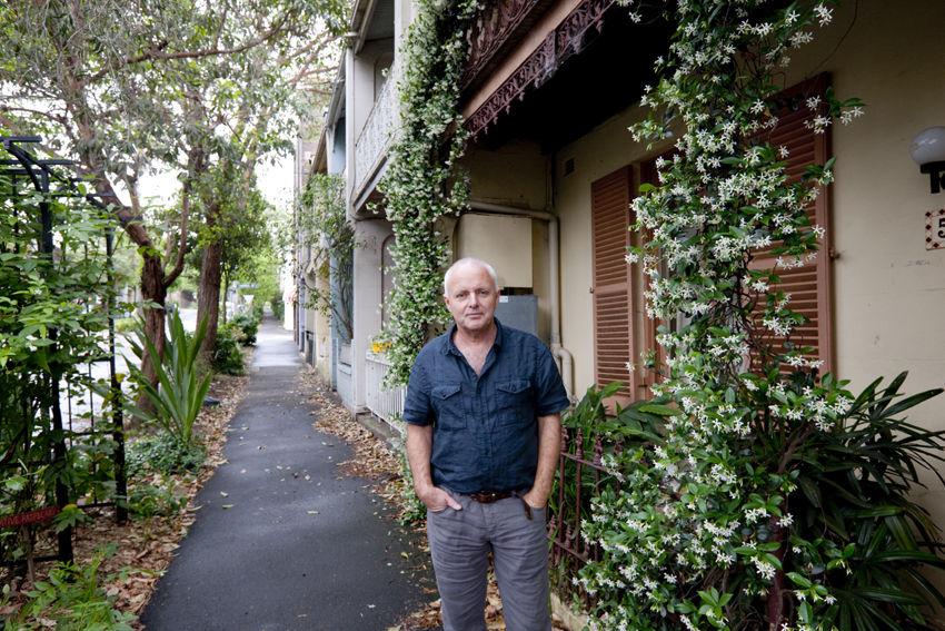 Michael Mobbs stands on the footpath outside his house. A vine climbs a pole next to him.