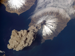 Aerial view of a volcanic island erupting smoke over the ocean
