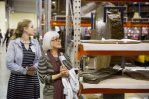 Older and younger woman walking past storage display units on a guided tour of MDC