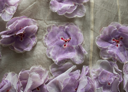 Purple textile flowers on white cloth background