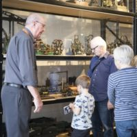 Family with small child looking at glass cabinet