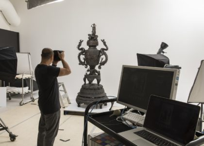Ryan Hernandez, Photography Coordinator, photographing object in studio with digital editing equipment in shot