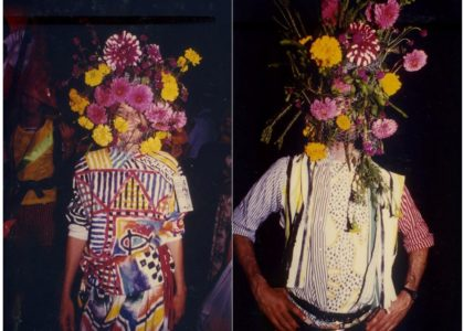 A photo of a man and a women with flowers covering their faces.