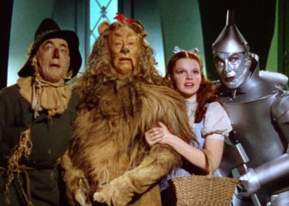 Four figures stand together, a man dressed as a scarecrow, a man dressed as a lion, a girl in a blue dress and white shirt and a man dressed as a tin-man
