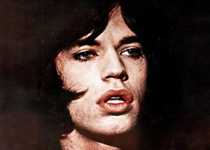 A close-up of Mick Jagger's face showing dark eyes, pouting lips and dark hair