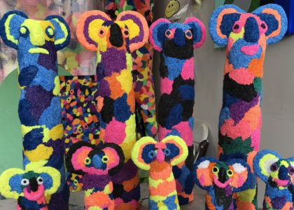 8 koala shapes are grouped together, made from brightly coloured materials.