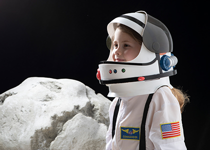 Small child in space suit next to space boulder
