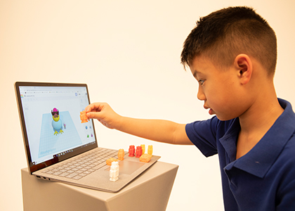 Small boy plays with 3D printed toy and computer