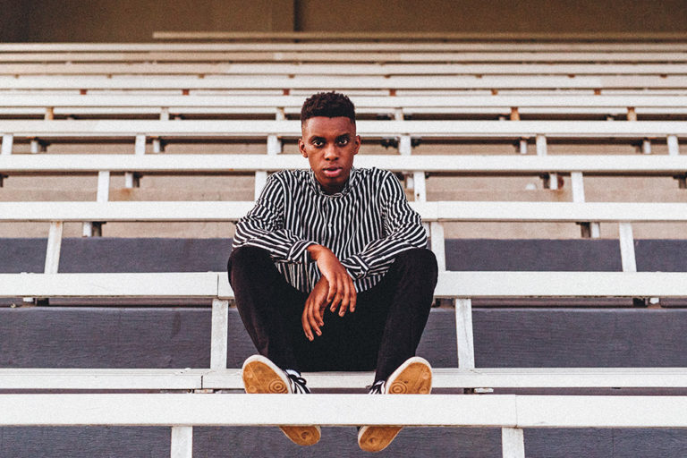 Photo of young man sitting in bleachers