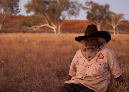 Indigenous elder Nyarri reclining in the Pilbara desert.
