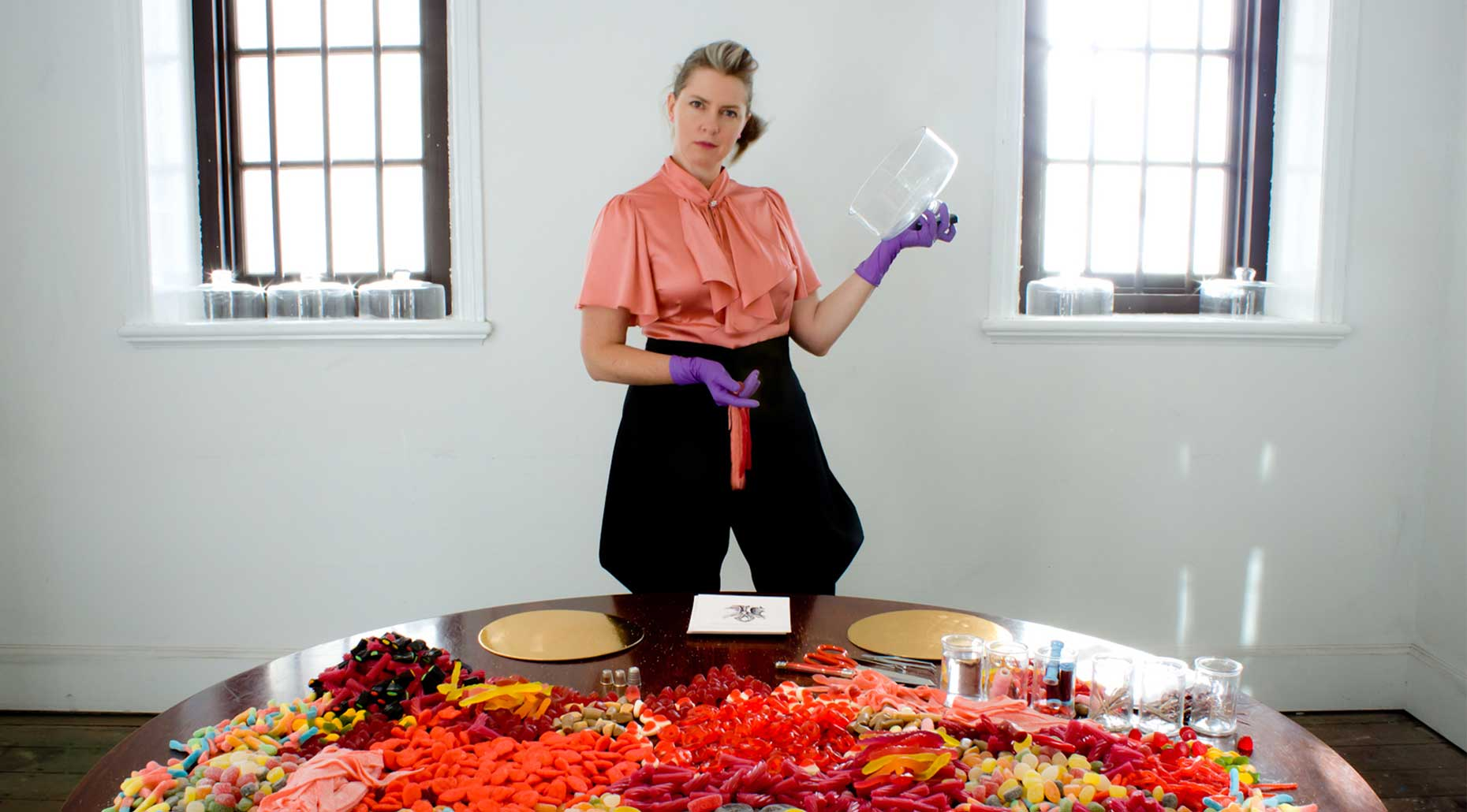 Cat Jones standing in front of a table with Anatomy Confection at Proximity Festival at Fremantle Art Centre in 2014. Image credit Cat Jones