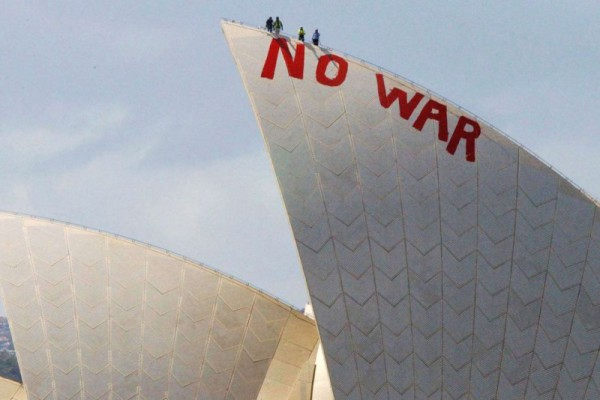 "Will Saunders and David Burgess climb the Sydney Opera House to paint the slogan ""NO WAR"", 2003, AAP Image/Mick Tsikas"