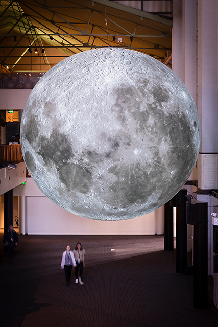 Large Moon hanging from ceiling, two people looking up at awe