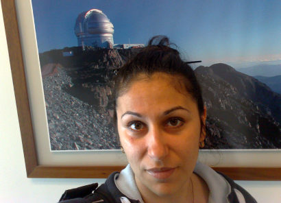 Aina in front of a picture of the Gemini South telescope