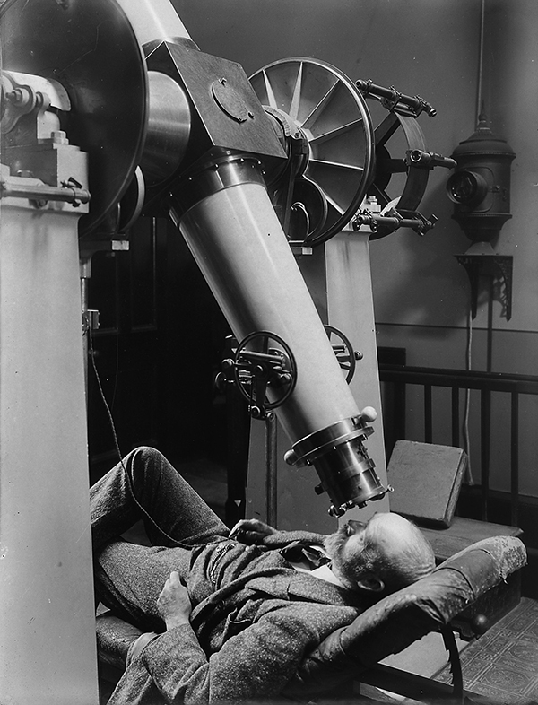 black and white image of a reclined man looking through a large telescope