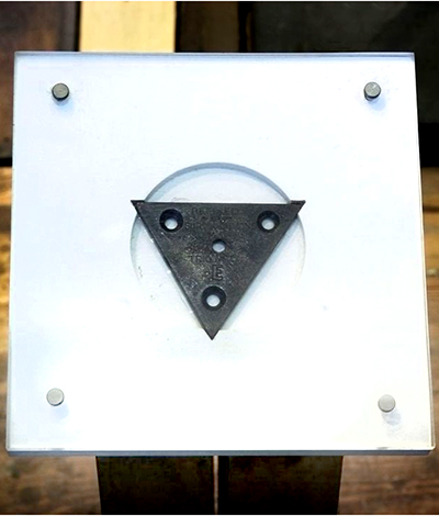 Triangular piece of metal with drill holes mounted on a white board
