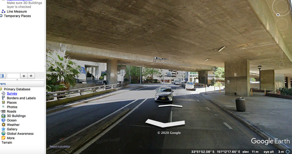 Colour photo of highway underpass with a palm tree fo the left hand side.