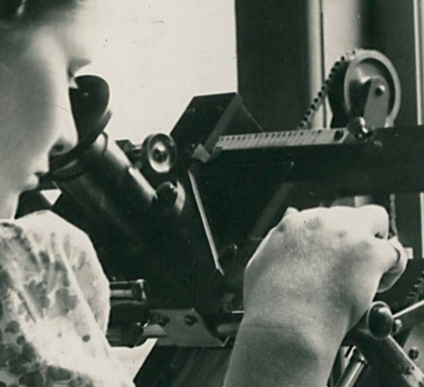 A black and white photograph of a woman looking through an eyepiece with a lens