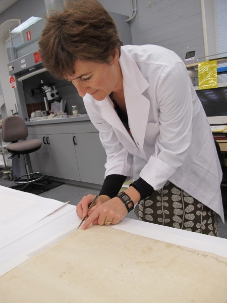 Conservator, Dee McKillop, trimming the japanese tissue repair