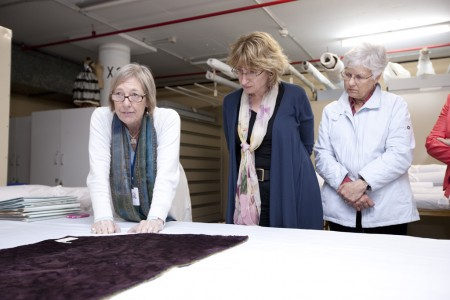 Visitor group examining textiles