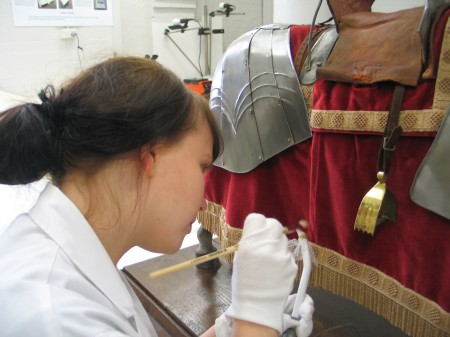 Conservator repairing red velvet cloth on the armored knight object