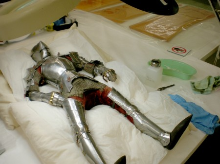 Armored knight laid out a white pillow with cleaning supplies around