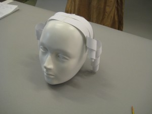 Side view of mannequins head with paper stripes on top of head