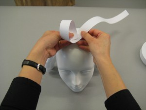 Folded paper being placed on top of mannequin's head
